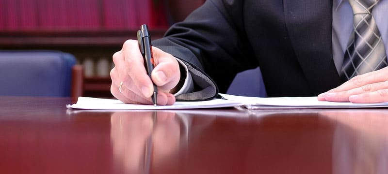 Man writing at desk during Court Reporting Process